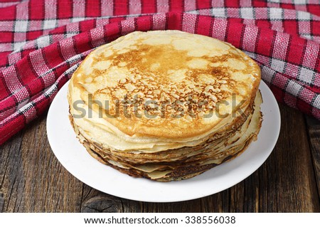 Stack of pancakes on old wooden table with red tablecloth
