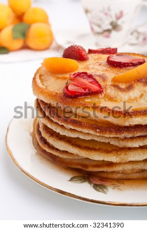 stack of pancakes slathered with syrup and coffee