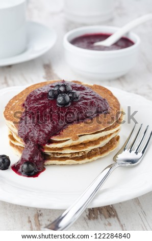 stack of pancakes with black currant jam on a plate for breakfast, closeup - stock photo