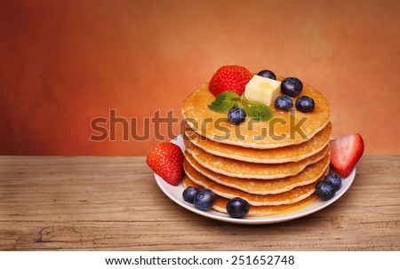 Stack of pancakes with fresh blueberry, strawberry and maple syrup - stock photo