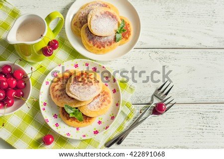 Stack of pancakes with fresh cherries on wooden background. - stock photo