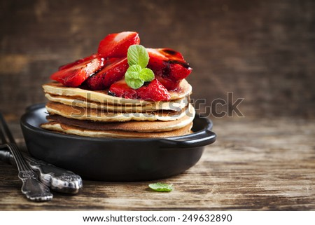 Stack of pancakes with fresh strawberry and balsamic glase in frying pan - stock photo
