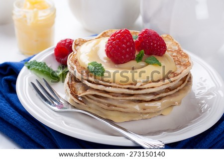 Stack of pancakes with homemade lime curd and fresh raspberries. Selective focus - stock photo