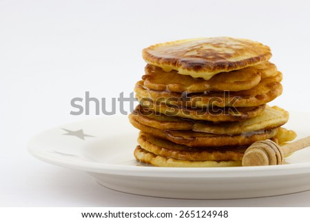 Stack of pancakes with honey on the plate isolated on white background  - stock photo