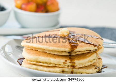 Stack of pancakes with maple syrup and fruit