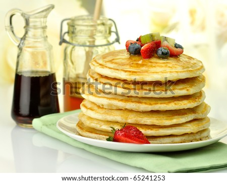 stack of pancakes with maple syrup,honey and berries - stock photo