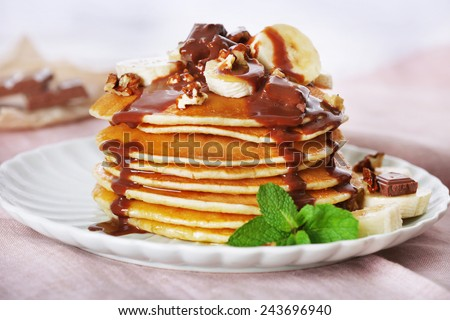 Stack of pancakes with mint, walnuts, chocolate and slices of banana on table with fabric on wooden planks background - stock photo