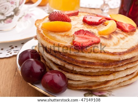 stack of pancakes  with syrup and fruit