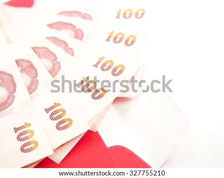 Stack of paper notes on red envelope, chinese culture, thai money, bonus or prize   - stock photo
