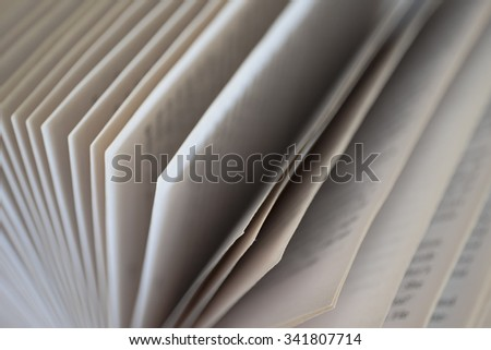 Stack of papers in a book with text and shallow depth of field - stock photo
