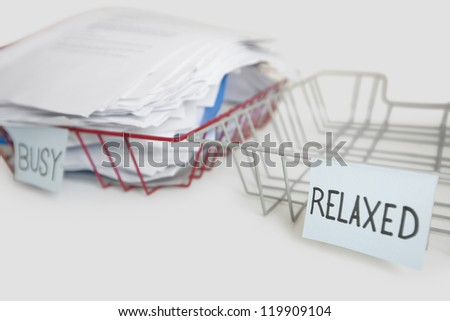 Stack of paperwork in busy tray with empty relaxed platter over white background - stock photo