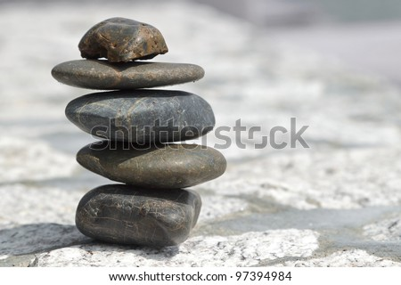 Stack of pebble stones on stone paving - stock photo