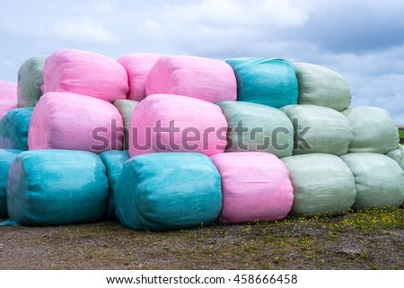 Stack of pink, blue and green silage bags - stock photo