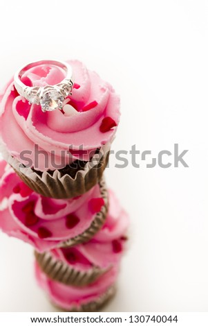Stack of pink cupcakes with engagement ring on top.
