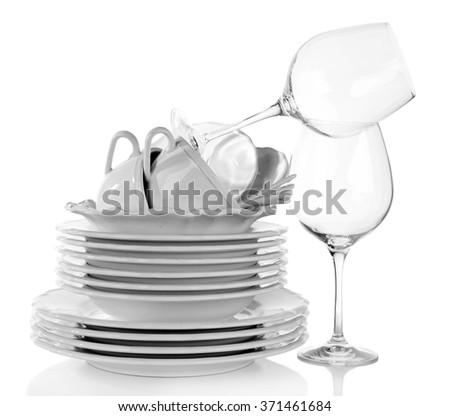 Stack of plates, cups and wineglasses on white background - stock photo