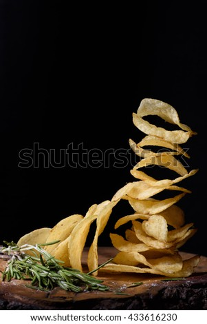 Stack of potato chips with herbs, tasty snack on wood, closeup. - stock photo