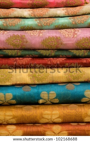 Stack of printed Indian silk fabric at a market
