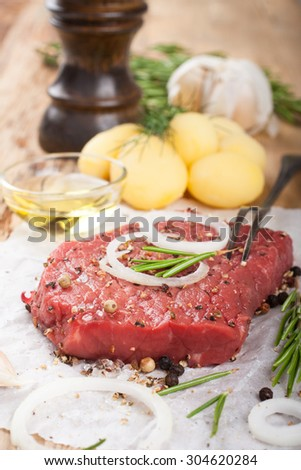 Stack of raw beef steaks and spices on old wooden background.  Healthy food concept. Selective focus. - stock photo