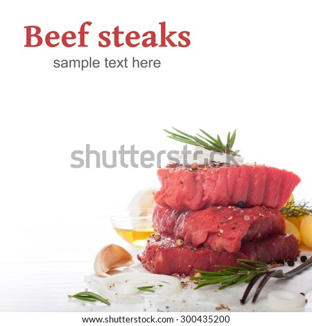 Stack of raw beef steaks and spices over white.  Healthy food concept with copy space with sample text. Selective focus. - stock photo