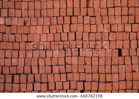 Stack of raw unbaked bricks made of red clay.