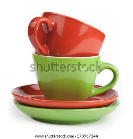 stack of red and green tea cups and saucers, isolated on white