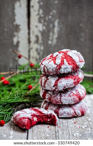 Stack of red velvet crinkle Christmas cookies with garland on a vintage wooden background - stock photo