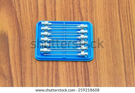 Stack of reuse iron needle No.18 G for drug needle in blue plastic on wooden floor - stock photo