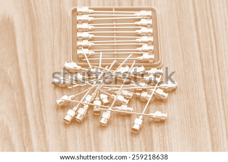 Stack of reuse iron needle No.18 G for drug needle in blue plastic on wooden floor process in tinted photo - stock photo