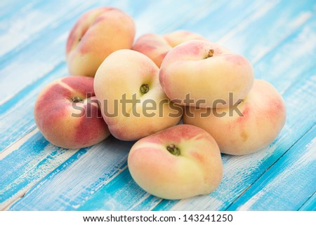 Stack of ripe donut peaches on wooden boards
