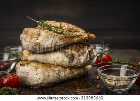 Stack of roast chicken breast with fried seasoning and tomatoes on dark wooden background - stock photo