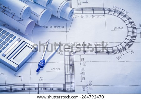 stack of rolled blueprints calculator compass construction concept  - stock photo