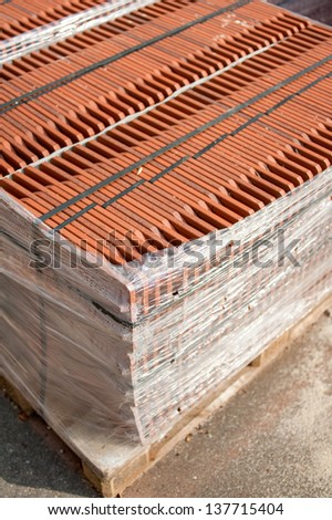 Stack of roofing tiles packaged on a wooden pallet on a construction site