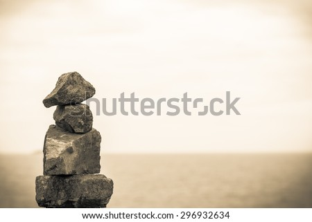 Stack of round smooth stones on a seashore. Business teamwork concepts. Seascape and blue sky.Vintage retro effect style pictures. - stock photo
