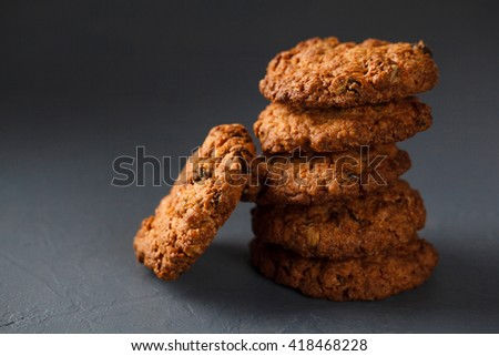 Stack of round wheat cookies with one cookie aside isolated on dark gray background. - stock photo