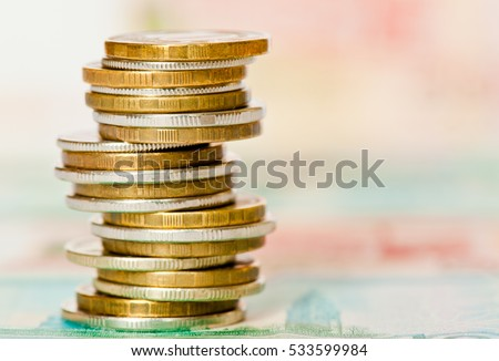Stack of rubles coins against 1000 and 5000 rubles banknotes background