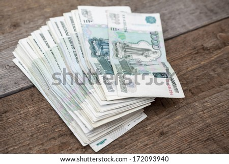 Stack of Russian thousandths notes on wooden floor - stock photo