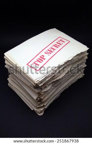 stack of secret documents on black background - stock photo
