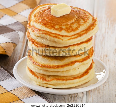 Stack of Small pancakes on a white wooden table.