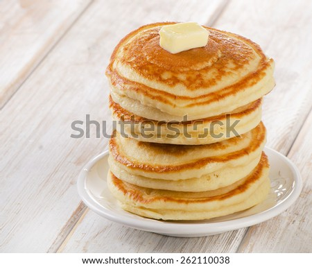 Stack of Small pancakes on  wooden table.