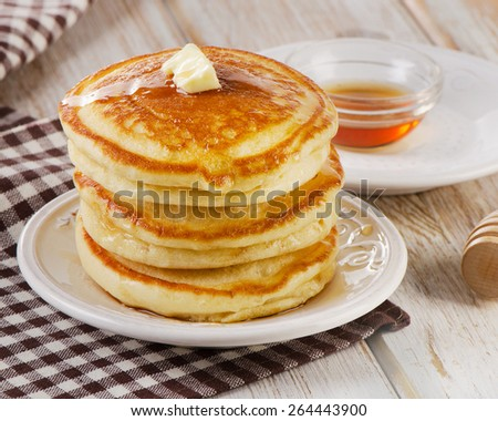 Stack of Small pancakes with a maple syrup.