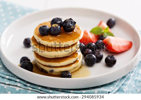 Stack of small pancakes with berries on a plate - stock photo