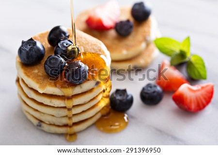 Stack of small pancakes with berries on marble board - stock photo