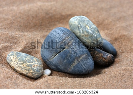 Stack of smooth pebbles on beach - stock photo