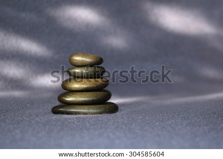 Stack of smooth stones against a serene grey background - stock photo