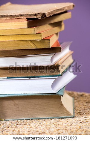 Stack of some old books piled on a table.  - stock photo