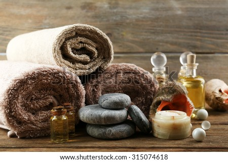 Stack of spa stones and spa treatments on wooden background - stock photo