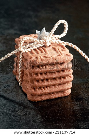 Stack of speciality speculoos biscuits, a spicy crunchy Dutch biscuit served for the feast of St Nicholas, and now enjoyed as a Christmas treat in many countries tied with string as a gift - stock photo