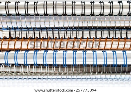 Stack of spiral paper notebooks with binding wire, stack of binders - stock photo