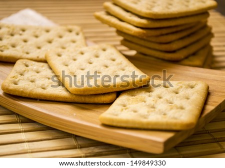 Stack of square crackers close-up on wooden mat. - stock photo