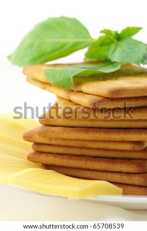 Stack of square crackers, slices of cheese and sweet basil in white plate on white background.